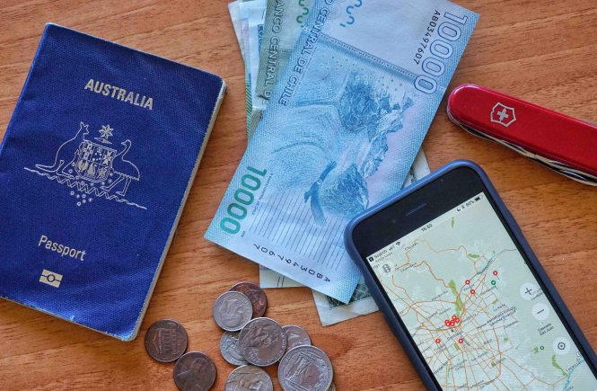Australian passport, cash, map and other travel items on desk.